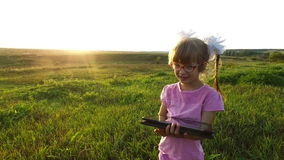 Little girl with enthusiasm plays on the tablet PC. Girl child with glasses stands on a green meadow. stock video