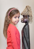Little girl with ethnic doll. Four year old girl with African doll-figurine Stock Photos