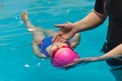 A little girl of European appearance in a pink rubber cap learning to swim in the pool.  Royalty Free Stock Image