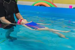 A little girl of European appearance in a pink rubber cap learning to swim in the pool.  stock photography