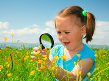Little girl examining flowers using magnifier Royalty Free Stock Photos