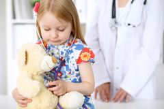 Little girl examining her Teddy bear by stethoscope. Health care, child-patient trust concept. Little girl examining her Teddy bear by stethoscope. Health care Royalty Free Stock Images