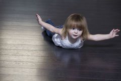 Little Girl Exercising On Floor Royalty Free Stock Photography