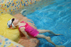 Little girl exercising while learning to swim Royalty Free Stock Photography