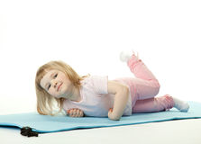 Little girl exercising lying on a training mat Stock Photo