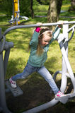 Little girl exercising on outdoor fitness machine Stock Images
