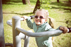 Little girl exercising on outdoor fitness machine Royalty Free Stock Photography