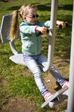 Little girl exercising on outdoor fitness machine Stock Photography