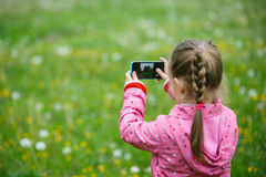 Little girl exploring nature with her smartphone. Little curious girl photographing with her smart phone, exploring nature and standing in a dandelion meadow royalty free stock photography