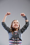 Little girl exulting raising her arms Stock Photos