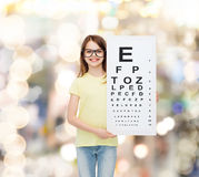 Little girl in eyeglasses with eye checking chart Stock Photo