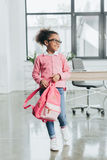 Little girl in eyeglasses holding pink backpack while standing indoors Stock Photo