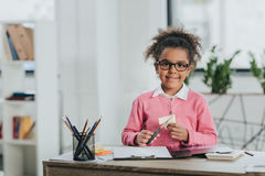 Little girl in eyeglasses holding scissors and smiling at camera royalty free stock images