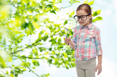 Little girl in eyeglasses with magnifying glass Royalty Free Stock Photography