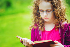 Little girl in eyeglasses reading the book in autumn park. Educa Royalty Free Stock Images