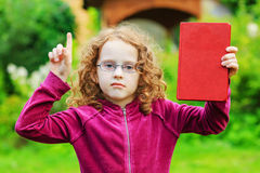Little girl in eyeglasses with red book and finger up. Royalty Free Stock Images
