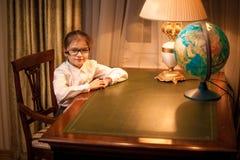 Little girl in eyeglasses sitting behind desk Stock Image