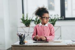 Little girl in eyeglasses sitting at table with office supplies. Serious little girl in eyeglasses sitting at table with office supplies Stock Photo