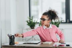 Little girl in eyeglasses sitting at table with office supplies. Serious little girl in eyeglasses sitting at table with office supplies Stock Images