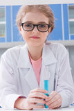 Little girl in eyeglasses and white coat holding test tube with reagent in lab Royalty Free Stock Image