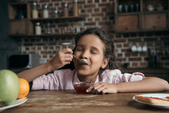 Little girl with eyes closed eating sweet jam from teaspoon. Portrait of little girl with eyes closed eating sweet jam from teaspoon Royalty Free Stock Photo