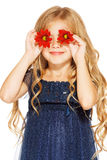Little girl with eyes - flowers. Little cute girl holding two red flowers near her eyes Royalty Free Stock Images
