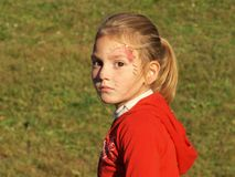 A little girl with a face makeup and a pensive look royalty free stock photos