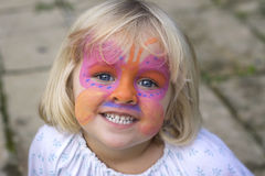 Little girl with face paint. A 4 year old girl smiling at the camera with a butterfly painted over her face Royalty Free Stock Photos