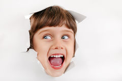 Little Girl Face through the Paper Hole. Cheerful Little Girl Face through the Hole of the White Paper stock photography