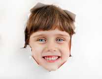 Little Girl Face through a Paper Hole. Cheerful Little Girl Face through the Hole of the White Paper stock photography