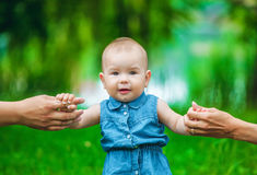 The little girl with a fair, short hair in a jeans dress without sleeves takes the first steps in park in warm, summer day, parent Royalty Free Stock Images