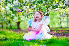 Little girl in fairy costume feeding a bird Stock Image