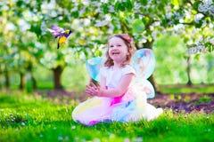 Little girl in fairy costume feeding a bird Stock Image