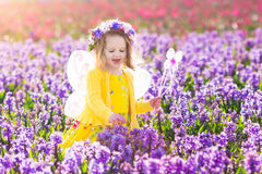 Little girl in fairy costume playing in flower field Royalty Free Stock Images