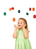 Little girl with falling easter eggs Stock Photos