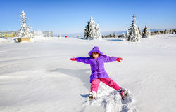 Little girl falling and having fun on the snow Royalty Free Stock Images