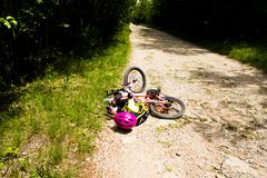 Little girl falling off her bicycle Stock Images