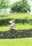 Little girl falling on stone wall Stock Images