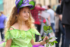 Little girl in fancy dress with a rose on the holiday Royalty Free Stock Images