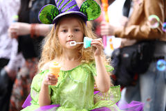 A little girl in fancy green dress blow soap bubbles Stock Image