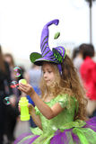 Little girl in fancy green dress catching soap bubbles Stock Photos