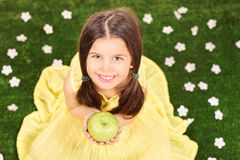 Little girl in fancy yellow dress holding an apple in a meadow f Royalty Free Stock Photos