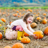 Little girl farming on pumpkin patch Stock Images