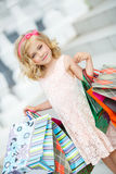 Little girl fashion with packages at the Mall. Royalty Free Stock Image