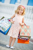 Little girl fashion with packages at the Mall. Royalty Free Stock Images