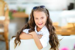 A little girl in fashionable glasses on the terrace background with long curly hair smiles in front of the camera stock image