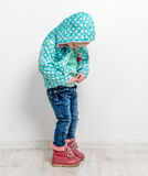 Little girl fastening her blue jacket Stock Photography