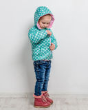 Little girl fastening her blue jacket. Little girl fastening her blue dotted jacket stock photo