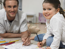 Little Girl With Father Coloring Book At Home Stock Image