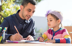 Little Girl And Father Drawing Pictures Together Stock Image